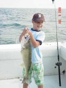 child holding bass in lake erie